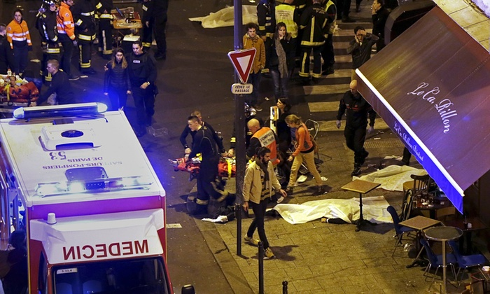 Fire fighters bringing an injured person out from the Bataclan Concert Hall